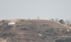 An India supporter waves his flag from a hill over looking the stadium.