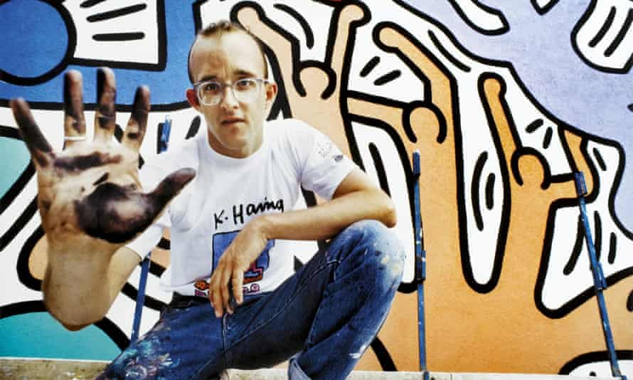 Keith Haring crouching in front of a mural.