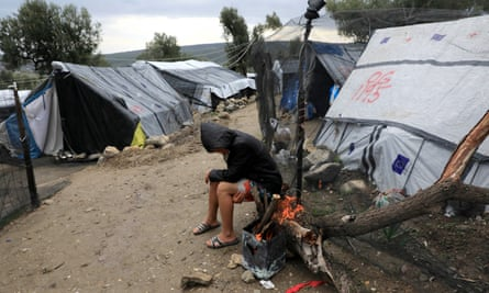 A refugee sitting by a fire at Moria camp