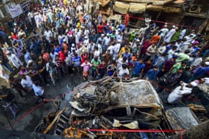People gather around the wreckage of cars that burnt in the devastating fire in Dhaka, Bangladesh that killed at least 80 people