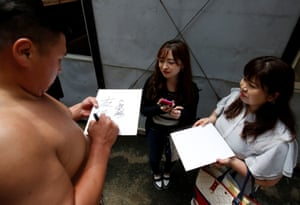 Tomozuna Oyakata, or master of the Tomozuna stable, signs autographs for fans after a training session at Ganjoji Yakushido temple in Nagoya, Japan in July 2017