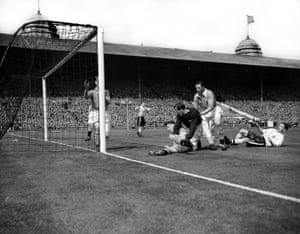 Farm and Fenton scramble the ball clear after Nat Lofthouse's shot hit the post.