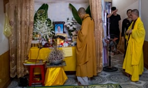 Family members and neighbours of Pham Thi Tra My attend a praying ceremony with Buddhist monks in front of a makeshift shrine.