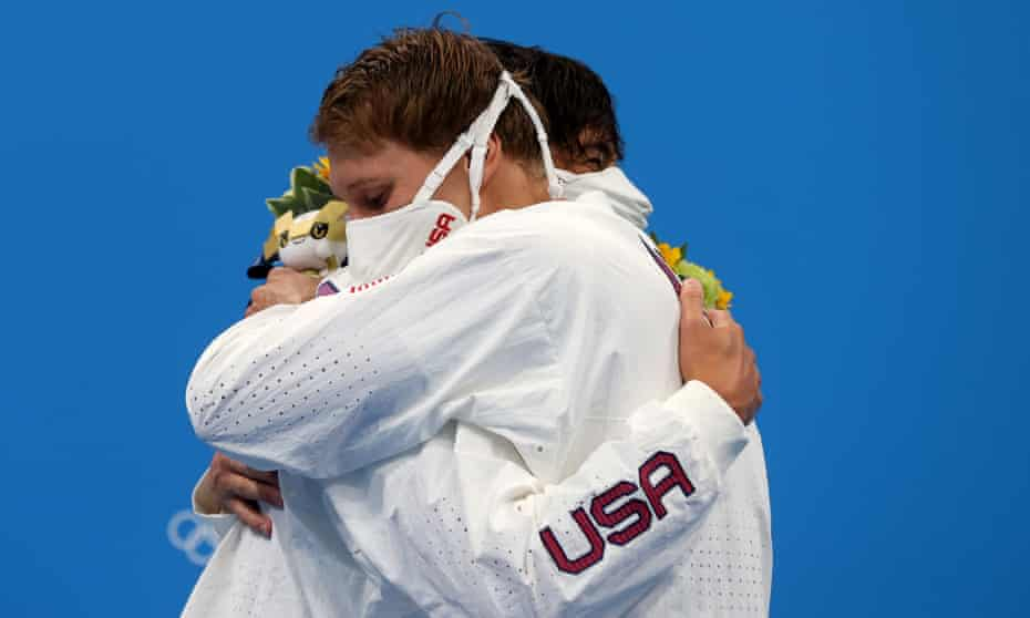 The US swimmers Jay Litherland (left) and Chase Kalisz embrace on the podium – which is in breach of Olympic Covid rules – following the men's 400m individual medley.