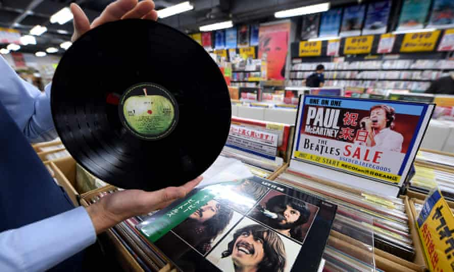 A Tokyo record store manager shows off a period Japanese pressing of The Beatles' final studio album Let It Be.