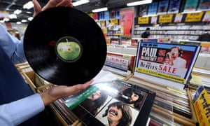 A shop manager shows off a period Japanese pressing of the Beatles' final studio album, Let It Be, at the RECOfan music shop in Tokyo's Shibuya district.