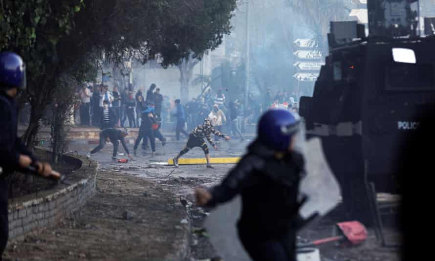 Anti-riot police officers clash with people protesting against president Abdelaziz Bouteflika in Algiers.
