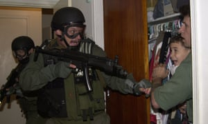 Armed US border patrol officers storm the house in Miama where six-year-old Elián González was being hidden by relatives, in April 2000.