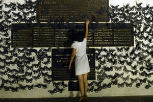 In San Salvador, the woman touches a memorial plate during a protest in commemoration of women murdered in El Salvador