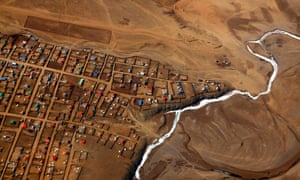 A frozen river is seen next to a group of houses on the outskirts of the Mongolian capital of Ulaanbaatar.