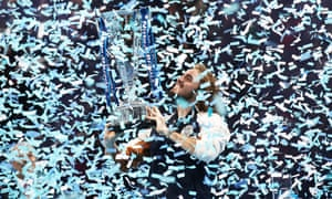 Stefanos Tsitsipas holds up the trophy as confetti falls after his defeat of Dominic Thiem.