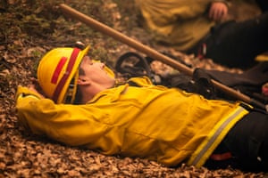 Rob Spitzer, a firefighter from Rancheria Station, rests in the smoldering forest after battling the Creek fire on 8 September.