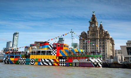 A Mersey Ferry designed by artist Sir Peter Blake sets sail across the river before the Liverpool city skyline.