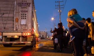 Heidi Menze, holding her daughter, Alexis, on her back, watches as a truck pulls in through the gate. It is carrying pigs destined for slaughter.