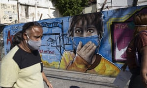 A man walks past a mural referencing the Covid-19 pandemic in Rio de Janeiro.