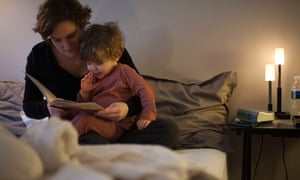 Mother holding toddler son on lap, reading bedtime story in bedC4TMHM Mother holding toddler son on lap, reading bedtime story in bed