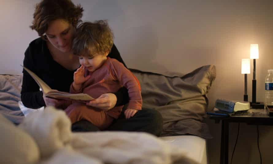 A mother reading to her child in bed