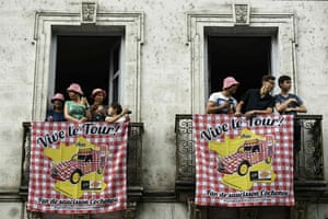 Supporters stand behind placards reading 'Long live the Tour !' from their balcony as they wait for the start of the tenth stage of the Tour de France