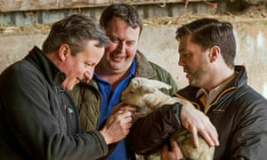 Stephen Crabb, right, holds a lamb as it is stroked by David Cameron on a visit to a farm in Wales.