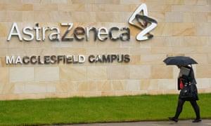 A woman walks outside British pharmaceutical company AstraZeneca in Macclesfield
