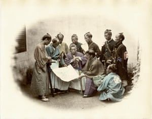 A group of samurai are shown gathered in discussion around a map