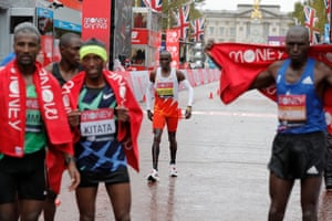 Kipchoge is spotted in the background while the winners celebrate.