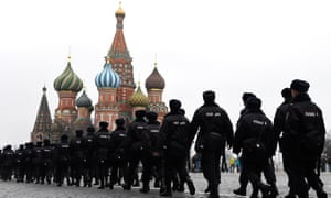 A long line of Russian police officers patrol Red Square with the Kremlin's towers in the background