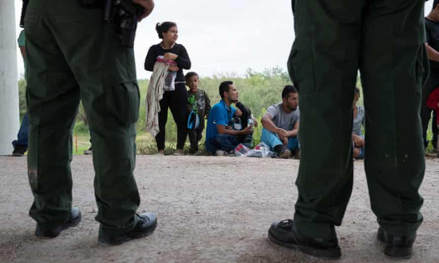US border patrol agents watch over a group of migrant families from Honduras and Guatemala as they wait for transportation a processing center after finding them near McAllen, Texas.