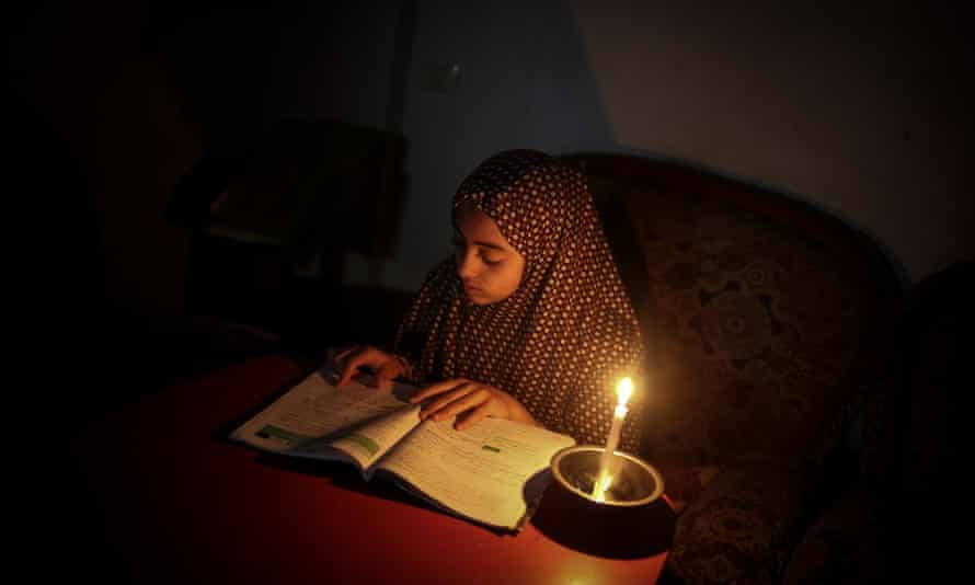 A Palestinian girl reads by candle light due to power cut at the Jabalia Camp in Gaza City