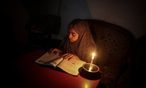 A Palestinian girl reads by candlelight after a power cut at the Jabalia camp in Gaza City