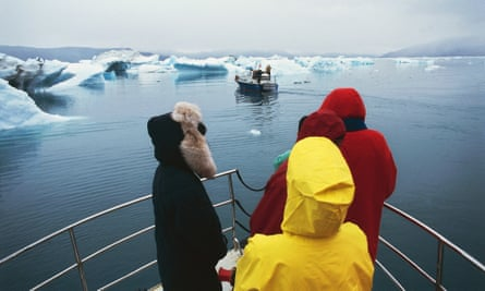 Tourists on bow of boat on a fjord in Greenland