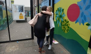 Staff members embrace as Kids Company closes its building in Camberwell, London.