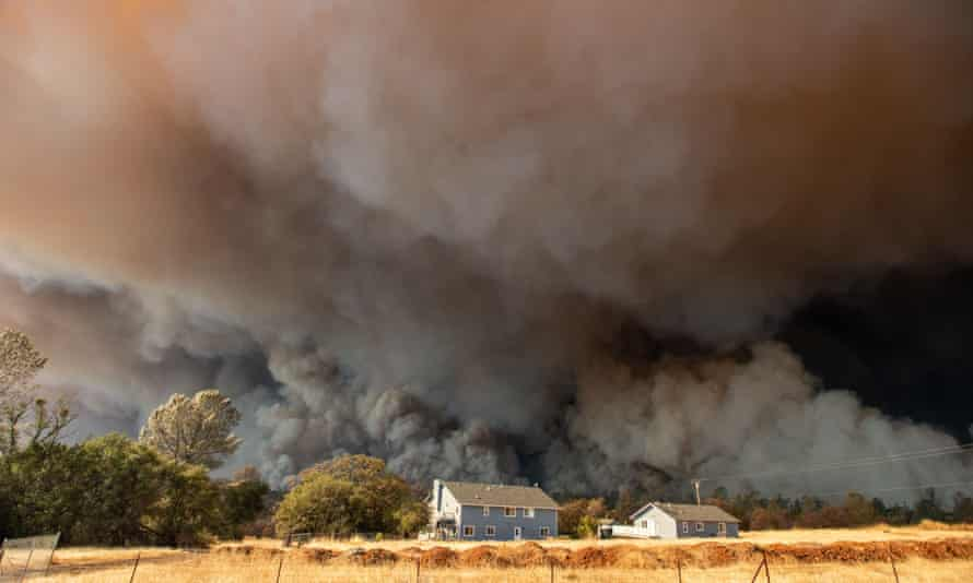 A home is overshadowed by towering smoke plumes in Paradise, California . Climate change-related risks will continue to grow without additional action, the report is set to warn.