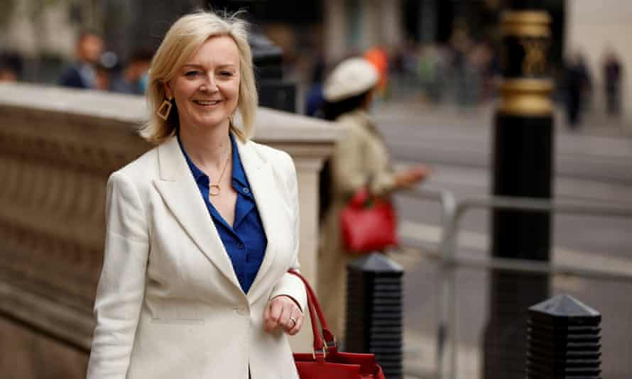 Liz Truss on the street, smiling at someone off camera, in London