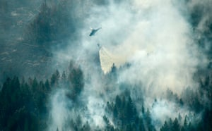 A firefighting helicopter drops water over the fire in Ljusdal, Sweden.