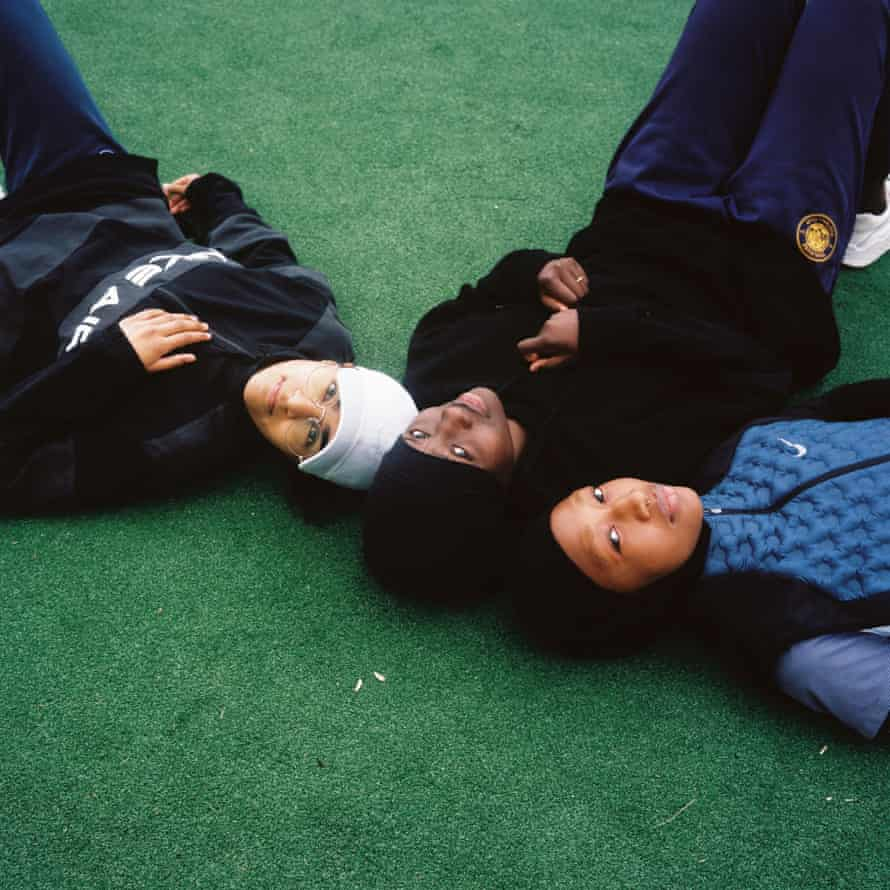 Les Hijabeuses (from left): Zamya, Diawara and Doucouré lie with heads together on the ground at Montreuil football pitch.