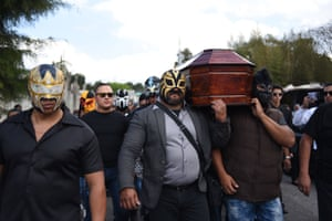 Wrestlers and relatives carry a coffin in Guatemala