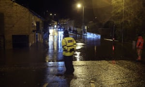 A police officer looks at flooding on Huddersfield Road in Stalybridge, Greater Manchester,