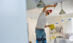 A man painting a ceiling