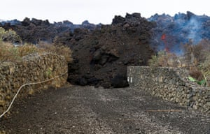 Lava blocks the driveway of a house