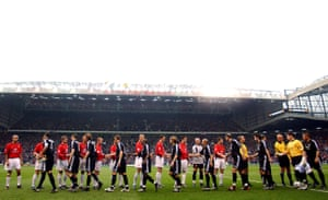 The players shake hands before kick-off at Old Trafford.