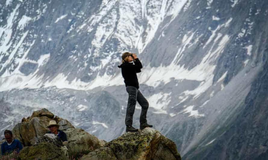 A trekker standing on top of a rock looking at a glacier through binoculars