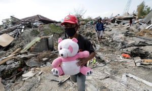 A person holds a stuffed toy in Petobo village, Palu