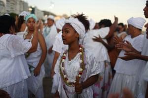 Believers of Afro-Brazilian religions pray to Yemanjá, the sea goddess of ancient Yoruba mythology and one of the most popular deities of Afro-Brazilian culture, on Copacabana beach.