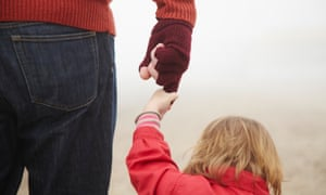 Young girl holding man's hand outside