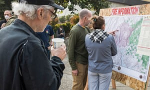 Residents locate their homes on a fire information map outlining the perimeter of the Camp Fire at the Neighborhood church evacuation shelter in Chico, California on 10 November.