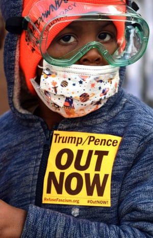 Washington DC, US. A young boy joins community members as they replace protest art on the fence surrounding the White House at Black Lives Matter Plaza after supporters of President Trump tore it down