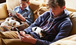 Boys using digital tablet and mobile phones with puppies sleeping in laps.