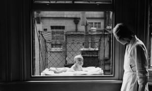 June 1937: A nanny supervising a baby suspended in a wire cage attached to the outside of a high tenement block window. The cages are distributed to members of the Chelsea Baby Club who have no gardens and live at the top of high buildings. (Photo by Reg Speller/Fox Photos/Getty Images) Baby cage