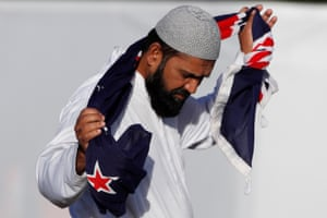 A man holds a New Zealand flag during a burial ceremony for victims of the attack
